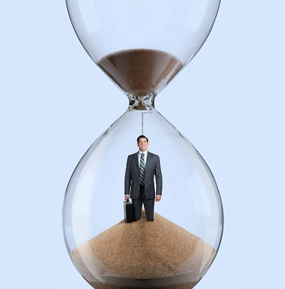 A businessman winces as he stands inside an hourglass while the sand pours on top of his head and buries him as time marches on.